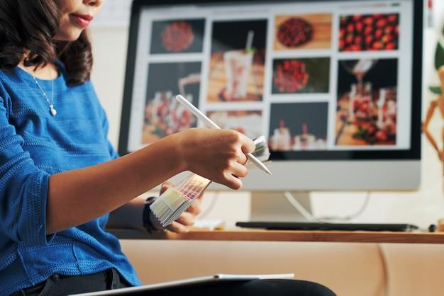 Close-up van serieuze aziatische ontwerper met pen die tegen computermonitor zit en kleur kiest op kleurstaal