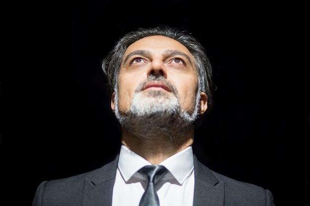 Close-up van serieuze zakenleider op zoek naar boven