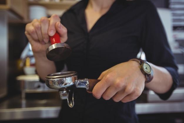 Close-up van serveerster die een sabotage gebruiken om gemalen koffie in een portafilter te drukken