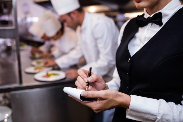Close-up van serveerster met blocnote in commerciële keuken