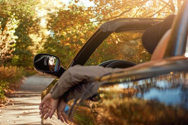 Close-up van sexy dame in hoed zit in cabriolet achteraanzicht