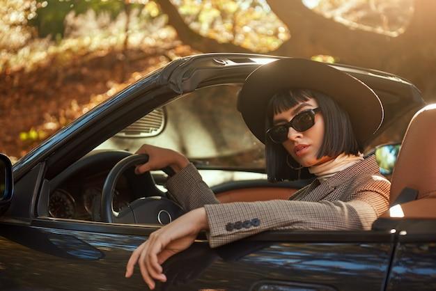 Close-up van sexy dame in zonnebril en hoed zit in cabriolet
