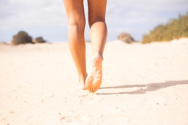 Close up van sexy naakt jonge mooie vrouw benen lopen op het zachte zand op het strand in vrije zomervakantie