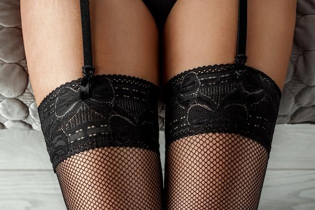 Close-up van sexy vrouwelijke benen in zwarte kousen. perfecte huid. seksleven concept, rollenspellen.