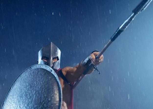 Close up van shirtless spartaans in harnas en rode mantel vechten buiten met speer. vooraanzicht van de man in de helm die het lichaam achter het ijzeren schild verbergt en het wapen omhoog wijst bij slecht bewolkt regenachtig weer.