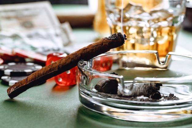 Close-up van sigaar en rode dobbelstenen kubussen gokken concept