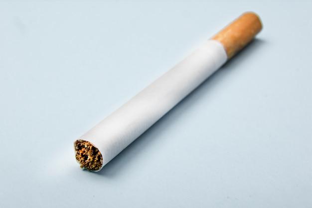 Close-up van sigaret op blauw wordt geïsoleerd dat