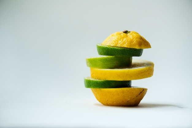 Close-up van sinaasappelen die met kalkstukken worden gemengd die op wit worden geïsoleerd