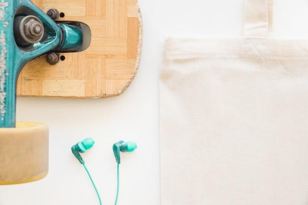 Close-up van skateboardwiel, oortelefoon en katoenen zak op witte achtergrond