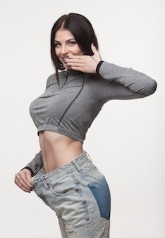 Close-up van slanke taille van jonge vrouw in grote jeans met succesvol gewichtsverlies