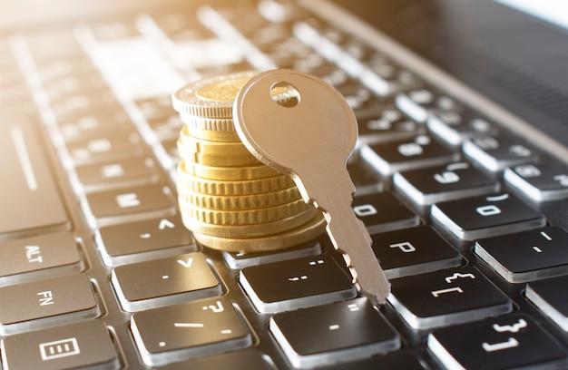 Close-up van sleutel en stapel munten op zwart toetsenbord. verzekering concept
