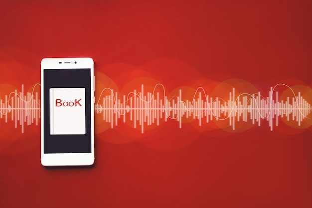 Close-up van slimme telefoon en audioboek op rode achtergrond met audiotrack. geluid, luister. audioboek-concept.