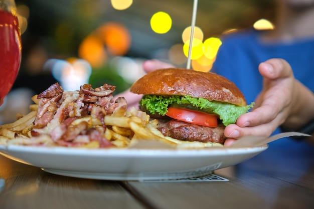 Close-up van smakelijke hamburger en frietjes met vlees op plaat in restaurant.