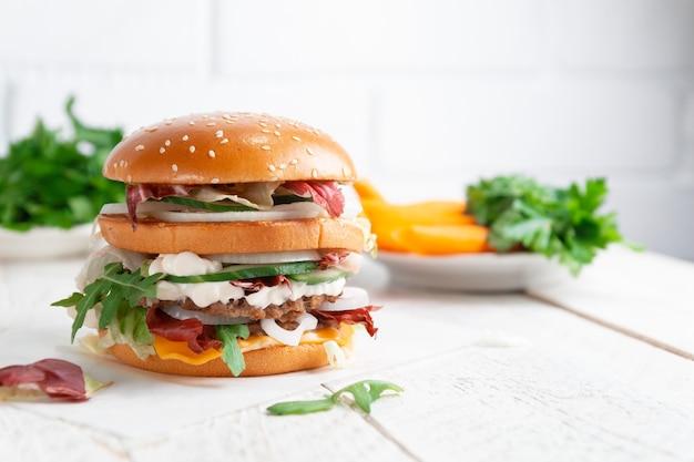 Close-up van smakelijke hamburger op een lichte houten van een bakstenen muur