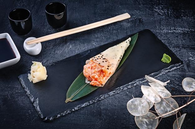 Close-up van smakelijke hand roll sushi in mamenori met zalm en tobico kaviaar geserveerd op donkere stenen plaat met sojasaus en gember. kopieer ruimte. temaki, japanse keuken. gezond eten