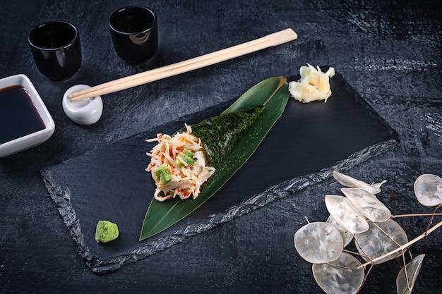 Close-up van smakelijke hand roll sushi met krab en tobico kaviaar geserveerd op donkere stenen plaat met sojasaus en gember. kopieer ruimte. temaki, japanse keuken. gezond eten