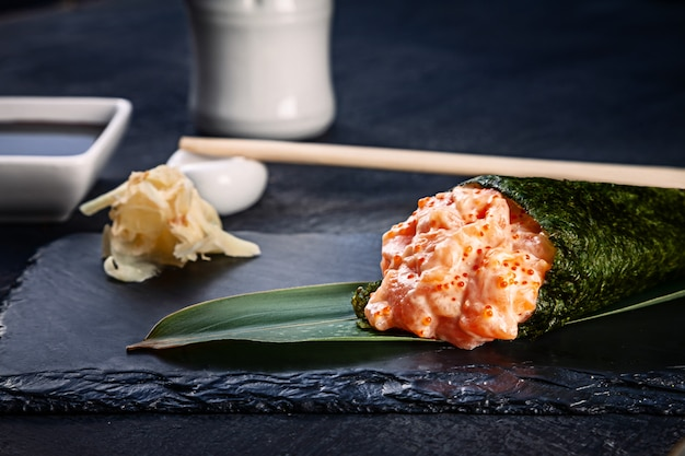 Close-up van smakelijke hand roll sushi met zalm en tobico kaviaar geserveerd op donkere stenen plaat met sojasaus en gember