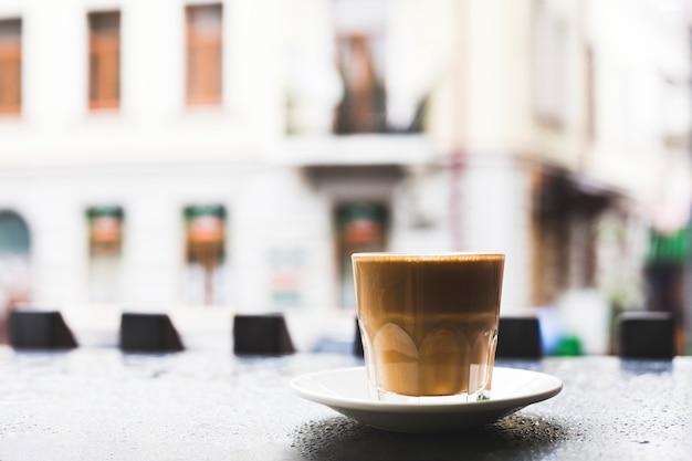 Close-up van smakelijke koffiekop met schotel op bureau