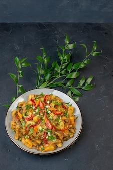 Close-up van smakelijke maaltijd met aardappelen en groenten groene bladeren op zwarte achtergrond met vrije ruimte