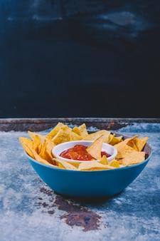 Close-up van smakelijke nachos en kom met salsa saus op metalen tafel