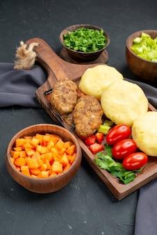 Close-up van smakelijke schnitzels gehakte groenten groenen op donker