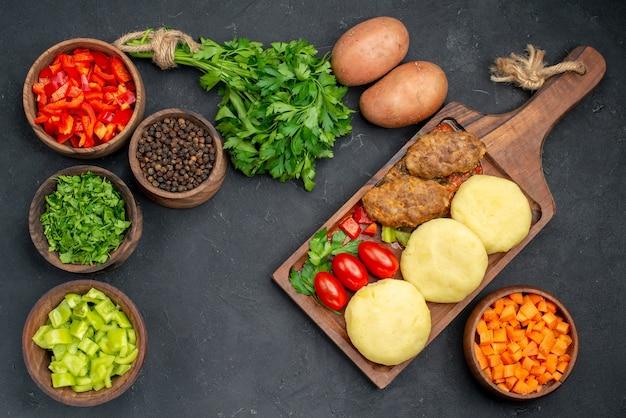 Close-up van smakelijke schnitzels met groenten en een bos van groen op donker