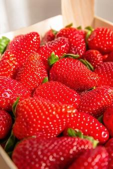 Close-up van smakelijke spaanse aardbeien, vers verzameld op een houten kist
