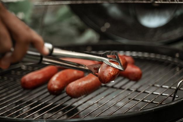 Close-up van smakelijke worstjes die op barbecuegrill op kolen worden gekookt. hand met vork wat betreft gegrilde worstjes. bbq-feestje. kampeervoedsel, ongezond voedsel. picknick onder de frisse lucht.