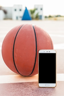 Close-up van smartphone en basketbal