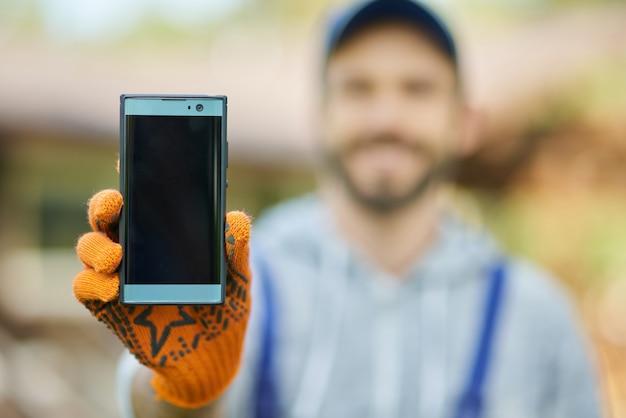 Close up van smartphone met leeg scherm jonge mannelijke bouwer in uniform met behulp van mobiele telefoon