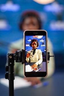 Close up van smartphone-opname vlog van afrikaanse influencer in thuisstudio. sprekend tijdens livestreaming, blogger discussiërend in podcast met koptelefoon op.