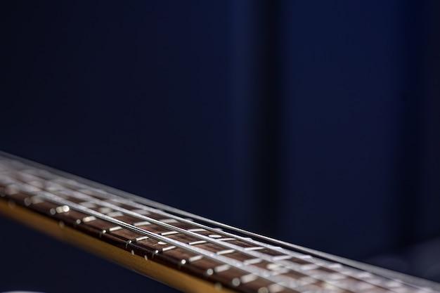 Close up van snaren op basgitaar op wazig zwarte achtergrond kopie ruimte.