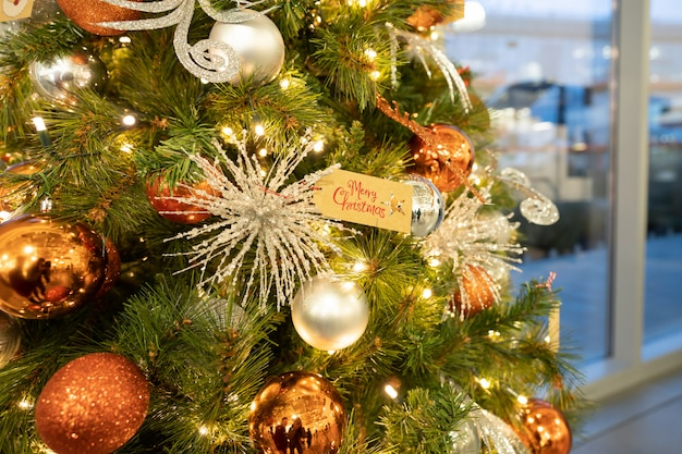 Close-up van snuisterijballen die van een verfraaide kerstboom hangen.