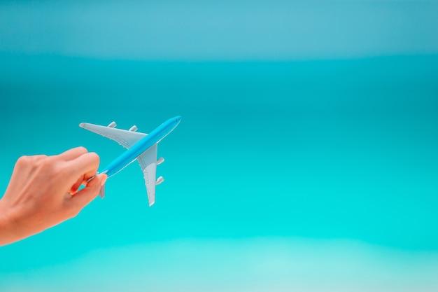 Close-up van speelgoed vliegtuig in hand achtergrond van de zee