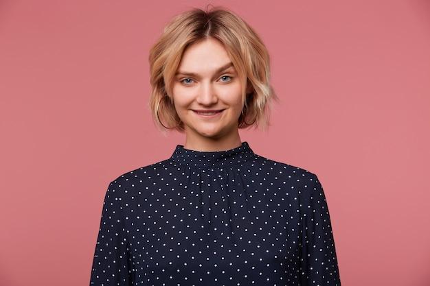 Close up van speelse jonge mooie aantrekkelijke blonde vrouw gekleed in blouse met polka dots, coquets, flirten, lip bijten toont aantrekkingskracht, geïsoleerd