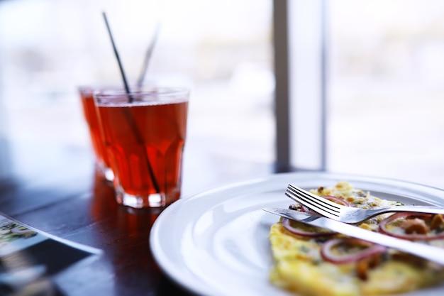 Close-up van spekpizza, sinaasappelsap in een glas op tafel in een café in een restaurant