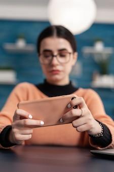 Close-up van spelershanden met smartphone in horizontale modus tijdens online shooter-competitie. concurrerende gamer zit aan bureautafel in de woonkamer, toernooi voor mobiele videogames