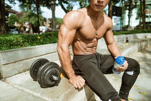 Close-up van spieren vormen een gespierde man wanneer hij zit met een drinkfles in de buurt van de halters na het trainen van zijn handspieren in het park