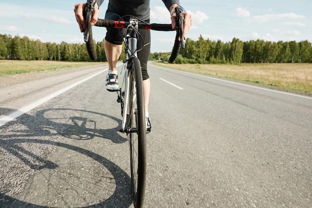 Close-up van sportfiets met atleet erop die buiten op een weg rijdt