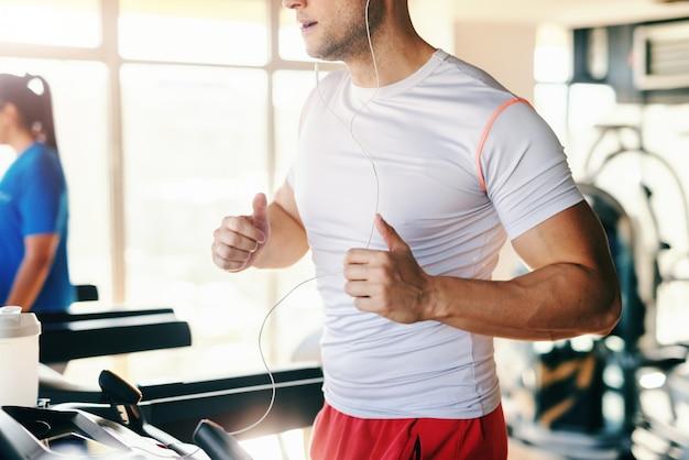 Close up van sportieve blanke man in sportkleding draait op de loopband in de sportschool. oortelefoons in de oren.