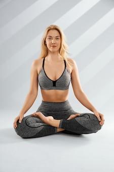 Close up van sportieve blonde jonge vrouw doet yoga praktijk geïsoleerd op grey