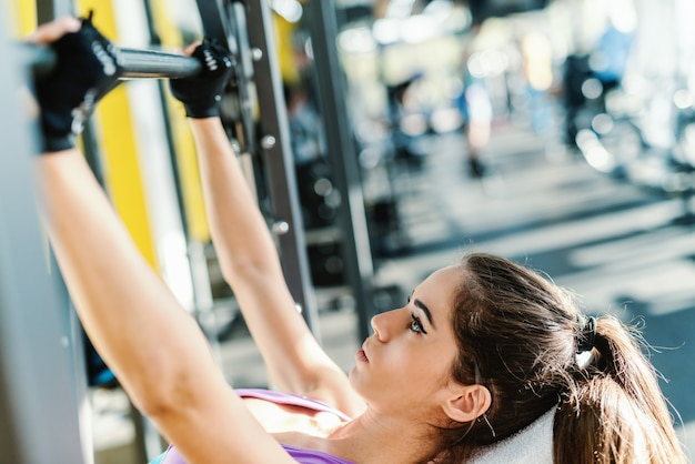 Close up van sportieve vrouw met paardenstaart en ernstige gezicht barbell opheffen terwijl liggend op de bank. gym interieur.