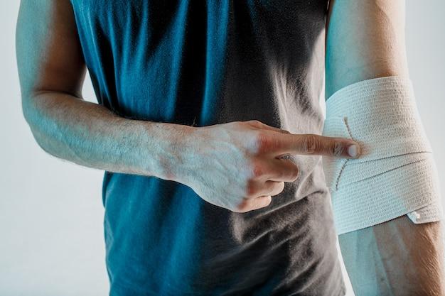 Close up van sportman inwikkeling medisch verband bij de hand. man draagt sportuniform. concept van sportblessure. geïsoleerd op turkooizen achtergrond. studio shoot