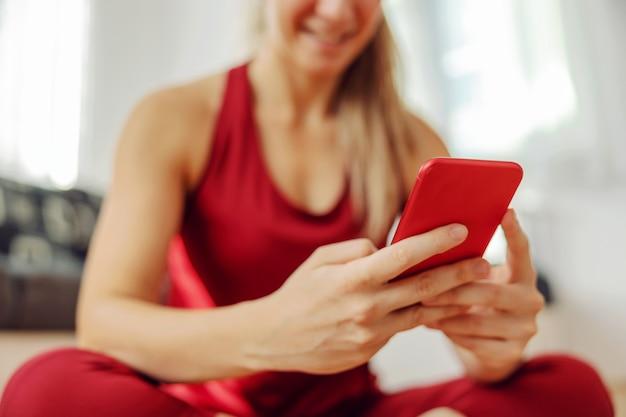 Close up van sportvrouw zittend op de vloer en met behulp van slimme telefoon.