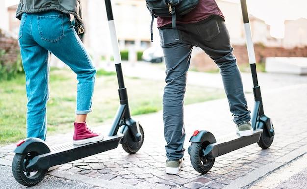 Close-up van stadsforenzen die een elektrische scooter gebruiken in het stadspark - millenial-studenten die een nieuw, modern ecologisch vervoermiddel berijden