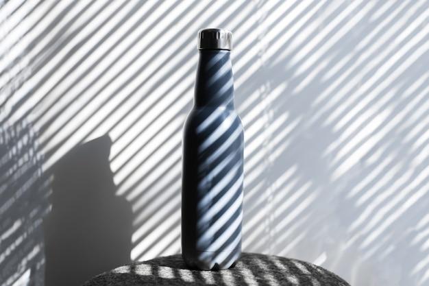 Close-up van stalen, eco herbruikbare thermo waterfles op achtergrond van schaduwen in de vorm van lijnen.