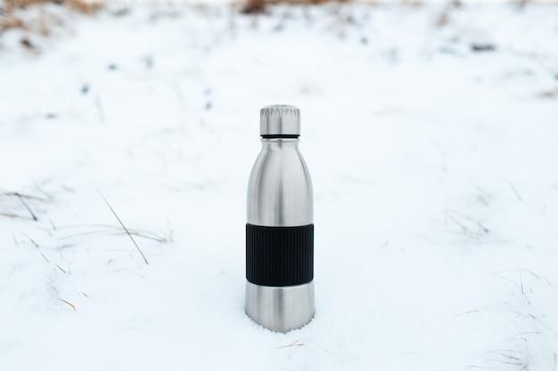 Close-up van stalen herbruikbare thermo waterfles in sneeuw. natuurlijke winterachtergrond.