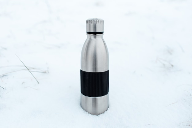 Close-up van stalen herbruikbare thermo waterfles in sneeuw.