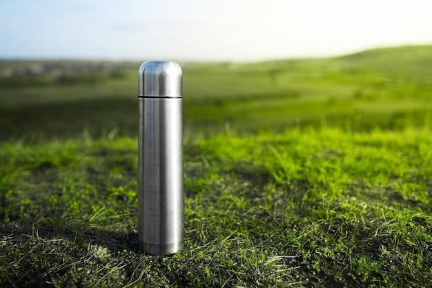 Close-up van stalen rvs thermoskan op groen gras met kopie ruimte.
