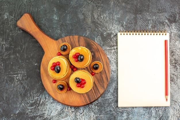 Close-up van stapel lekkere pannenkoeken op snijplank en notebook